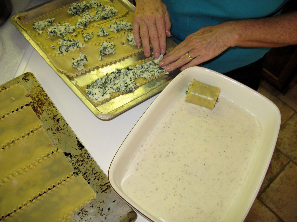 Spreading ricotta/spinach mixture on noodles (bechamel sauce in foreground)